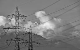 Strommasten in Landschaft mit Schneebergen und Wolken