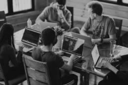 mehrere Personen mit Laptop an Coworking space