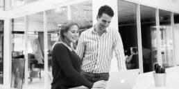 Zwei Kollegen stehen am Laptop und lächeln