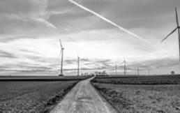Windkraftanlagen links und rechts neben Feldweg