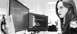 Frau vor Doppelbildschirm am Arbeitsplatz
