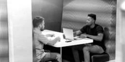 Zwei junge Männer im Co-workingspace mit Laptop