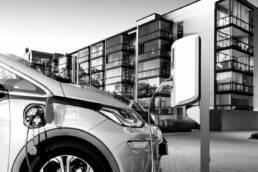 Elektroauto an Ladesäule, moderne Immobilien im Hintergrund