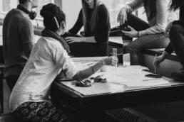 Junge Menschen sitzen am Tisch und diskutieren